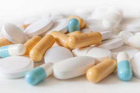 gros plan de capsules et de comprimés de drogue sur fond blanc