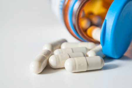 closeup of capsules and drug tablets falling from bottle on white background
