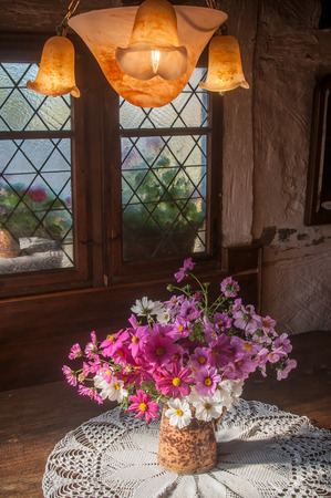 closeup of beautiful bouquet of flowers in vintage interior of alsatian house on stained glass background