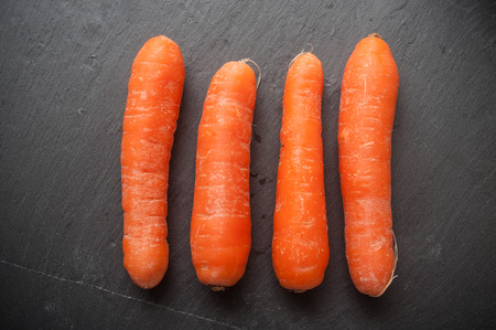 closeup of carrots alignment on chalkboard background Stock Photo