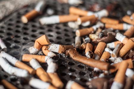 closeup of cigarette butts in a public ashtray