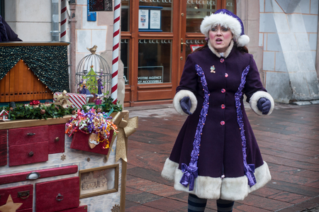 Mulhouse - France - 20 December 2017 - show with couple of traditional musician and singer with purple  leprechaun costume at the christmas market Editorial