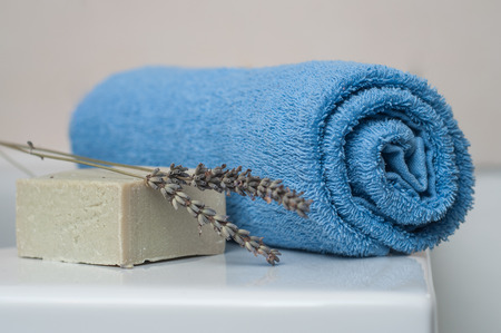 closeup of lavender soap and rolled blue towel in the bathroom