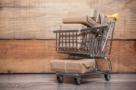 Closeup of mini trolley full of parcels to send on wooden background