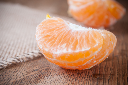 closeup of peeled tangerine on wooden background