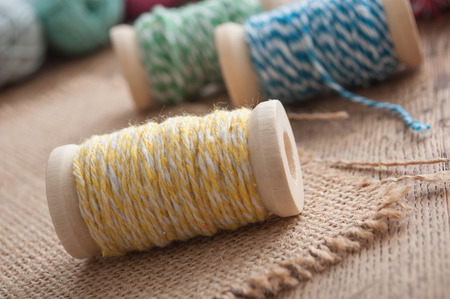 closeup of sewing thread spool bobbin on wooden table background