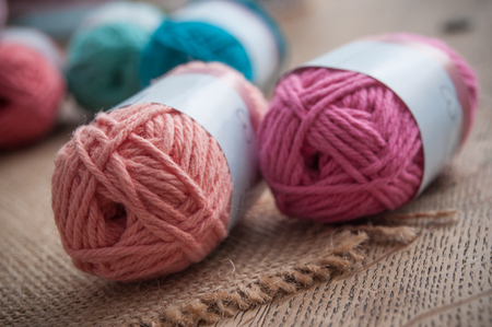 closeup of colorful wool balls on wooden table background