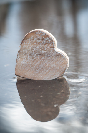 closeup of reflection in a puddle of wooden heart - Love concept  Stock fotó