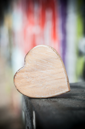 closeup of wooden heart  in outdoor on blurred graffiti wall background - Love concept