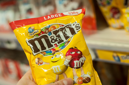 Mulhouse - France - 8 February 2018 - closeup of chocolate-coated peanuts from M & ms brand in hand at Super U supermarket Editorial