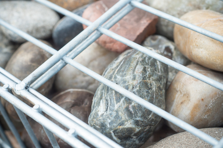 closeup of metallic basket net filled by natural cobbles as a gabion fence Stock Photo