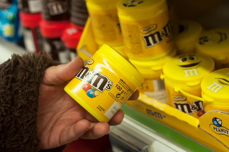 Mulhouse - France - 26 February 2018 -  closeup of chocolates from m& ms brand  in hand at Cora Supermarket