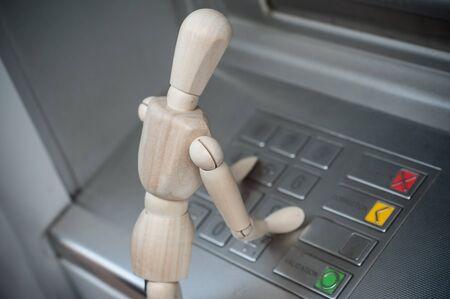 Closeup of wooden character in outdoor - concept withdrawal of money Standard-Bild
