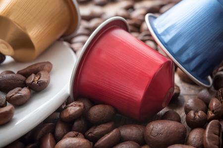 Nahaufnahme von bunten Espressokaffeedosen mit Kaffeebohnen auf Holztischhintergrund Standard-Bild