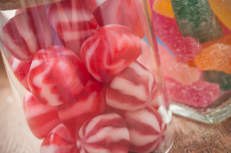 closeup of traditional red and white candies  in glass container on wooden table background