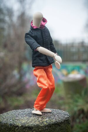 closeup of wooden puppet with street clothes in outdoor on graffti wal background - concept break dancing