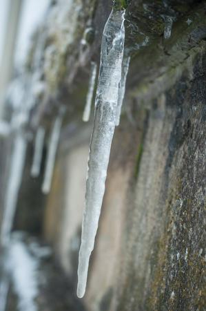 closeup of ice stalactites on stoned wall