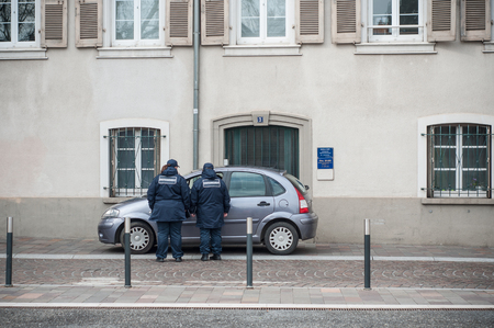 Mulhouse - France - 20 March 2018 - police women asking an autommobillist to leave his parking lot on the trestle