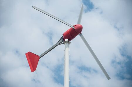 closeup of little wind mill for private electricity production on cloudy sky background