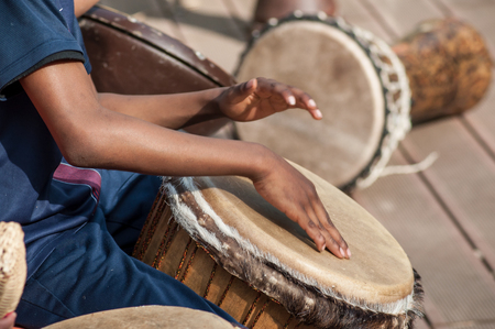 Closeup of kid's hands on African drums in outdoor
