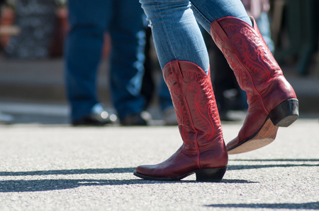 closeup of woman legs with red american boots at country show in outdoor  Banque d'images