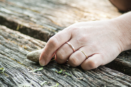 closeup of hand of womanwith pebble    for balance on wooden table Stock Photo