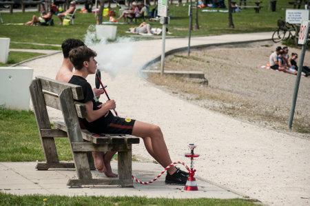 Reiningue - France - 21 May 2018 - two boys smoking shisha on wooden bench in border lake