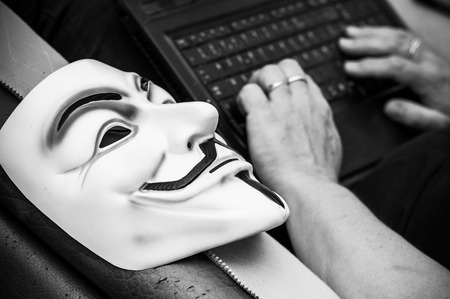 Paris - France - 19 May 2018 - Vendetta mask on old armchair in abandoned  factory with woman on background with computer  . This mask is a well-known symbol for the online hacktivist group Anonymous Editorial