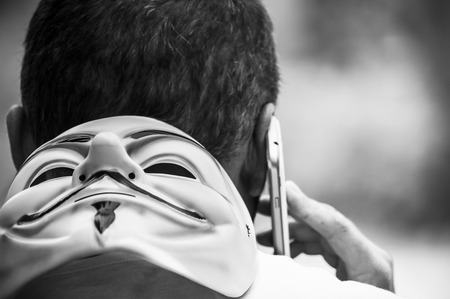 Paris - France - 19 May 2018 - portrait of man with Vendetta mask and telephone in outdoor. This mask is a well-known symbol for the online hacktivist group Anonymous