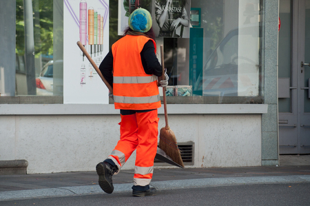 Mulhouse - France - 3 June 2018 - Woman municipal employee walking with shovel and broom in hand Banque d'images - 104639762