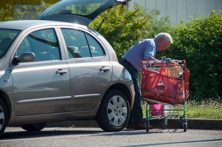 Mulhouse - France - 21 June 2018 - old man walking with trolley on supermarket parking storing his packages in his car