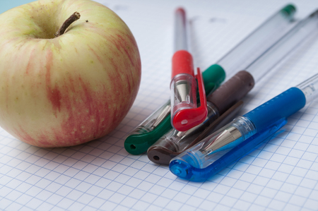 closeup of colorful ballpoint pens and apple on note book background