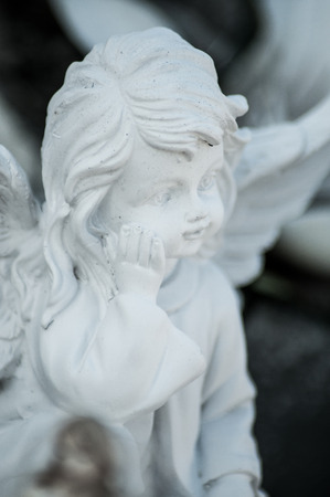 Closeup of stoned angel on tomb in cemetery