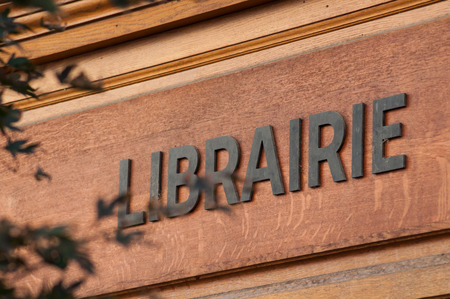 closeup of french bookstore ( librairie in french) signage on wooden vintage facade