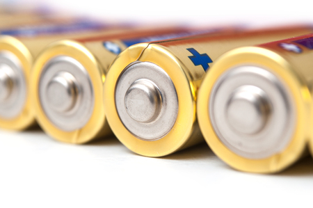 Closeup of golden and silver AA alkaline batteries group on white background Standard-Bild