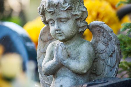 Nahaufnahme eines gesteinigten Engels auf einem Grab auf einem Friedhof auf gelbem Blumenhintergrund Standard-Bild