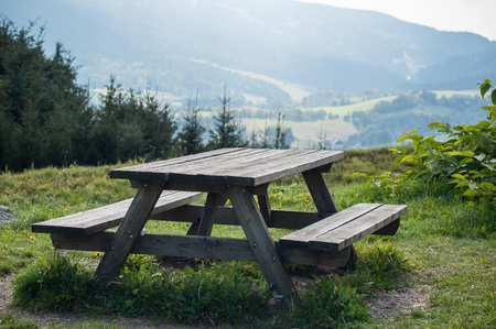 closeup of wooden picnic table in mountain landscape background