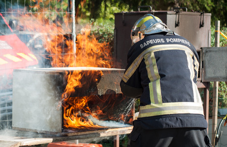 portrait of french fireman showing how to extinguish a fire