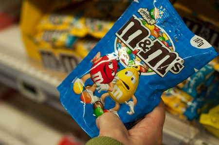 Mulhouse - France - 22 February 2018 - closeup of chocolate-coated peanuts from M & ms brand in hand at Super U supermarket
