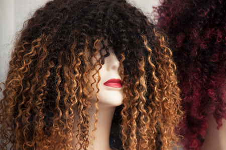 closeup of woman face of mannequin with afro wig in fashion store showroom Reklamní fotografie