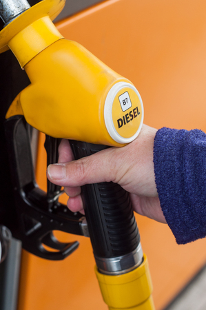 closeup of hand of woman taking gas pistols in gas Station