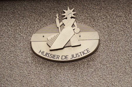 closeup bailiff plate on french building facade - huissier de justice ( text in french) traduction in english : bailiff