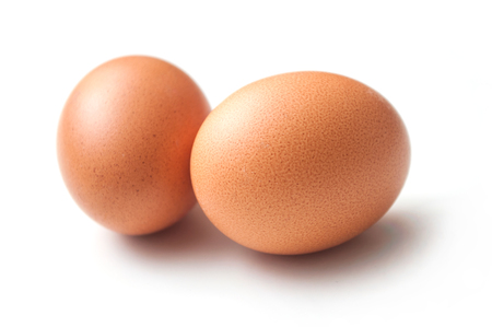closeup of two organic eggs on white background Imagens
