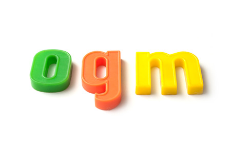 closeup of colorful plastic letters on white background - ogm