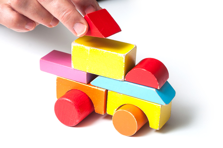closeup of woman skowing with hand a vehicle on colorful wooden blocks on white background