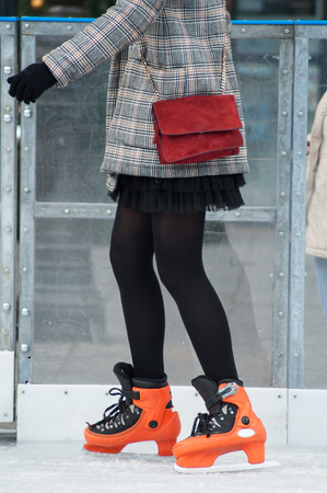 retail of legs of girl with mini black skirt and black tights slipping on an ice christmas rink Imagens