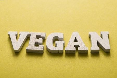 closeup of wooden letteers on yellow background with word  : Vegan