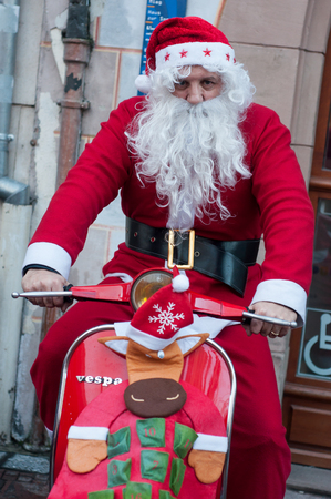 Mulhouse - France - 16 December 2018 - Man with santa claus costume on red scooter in the street at the christmas market