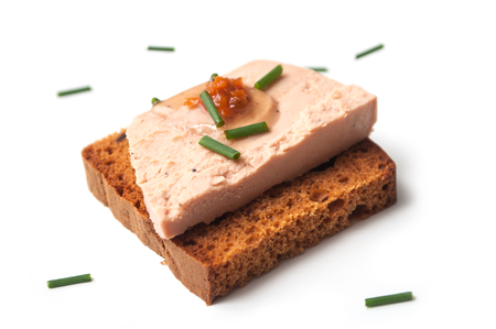 closeup of foie gras on gingerbread on white background