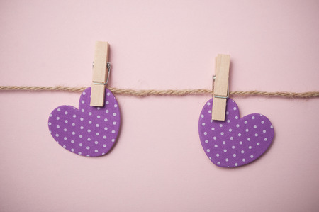 closeup of two purple hearts on clothespins on pink background - Valentine's day concept